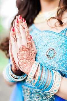 Indian bride wearing a blue lengha outfit + henna doing namaste - a must have pic