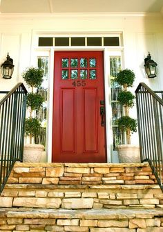 Red front door - A must-have. Topiaries, stacked stone stair steps, wrought iron, sconces... Eclectic exterior by Rachel Greathouse
