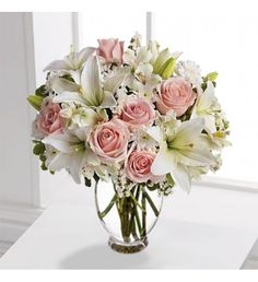 Beautiful arrangement of light pink roses, white asiatic lilies, white alstroemeria and white cushion spray chrysanthemums are mixed with white statice and variegated pittosporum in a clear glass vase.