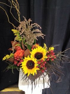 Fall is on the horizon in our flower shop with this gorgeous sunflower arrangement with autumn floral accents.