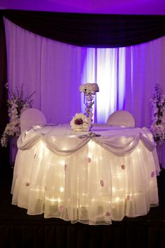 I like the lights under the tablecloth. Maybe we could find some tan tulle and put lights underneath it?