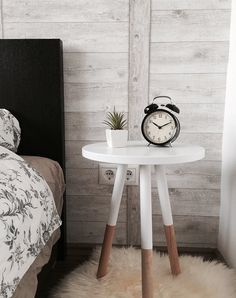 bedside table next to bed with alarm clock