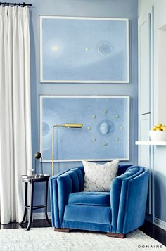Dusty blue walls with artwork and small gold lamp