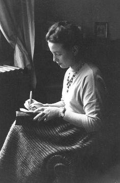 Simone de Beauvoir, the day of the Prix Goncourt, next to a window writing, Paris, 1954. Photo by Gisele Freund. °
