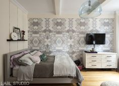 A small, feminine, studio rental apartment featuring hand-painted watercolor pinstripe walls, and a feature wall with Gemma Sapphire removable wallpaper from LABLstudio's Femme and Gem Collection. The space features a Kartell FLY pendant, a West Elm Wood Tiled Dresser for storage, and a West Elm bed that was painted gray. This Upper West Side studio is decked in out in ethereal, global, glam style. Interior Design by LABLstudio.