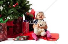 view of a cheerful baby girl with teddy bear sitting by christmas gift box and christmas tree. - View of a cheerful baby girl with teddy bear sitting by Christmas gift box and Christmas tree over white background. Model: Hannah Phillips