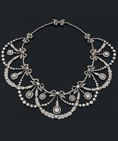 An important Belle Epoque platinum, gold and diamond 'draperie' necklace. Composed of seven ribbon and garland segments, entirely set with old-cut diamonds.