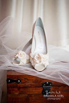 beautiful photography of wedding shoes with roses on a trunk with a bridal veil by © Radmila Kerl wedding photography munich schönes Bild von Hochzeitsschuhen mit Stoffrosen auf einer Truhe und Brautschleier