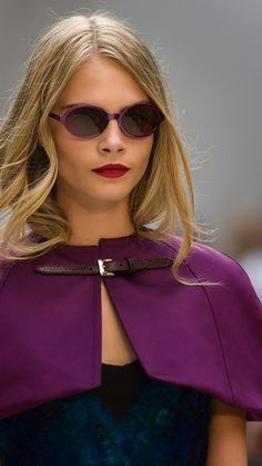 Cara Delevingne wearing a tailored satin capelet and Splash Sunglasses on the Burberry S/S13 runway