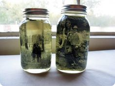 """DIY: """"Vintage"""" Photo Mason Jar Centerpiece Quart-sized Mason jar with lid  4″ X 6″ black-and-white photo (use the self-serve photo kiosk at Walgreens to transform a color photo into black-and-white or sepia)  Vegetable oil  Glue that dries clear  Pebbles or dried flowers (optional)"""