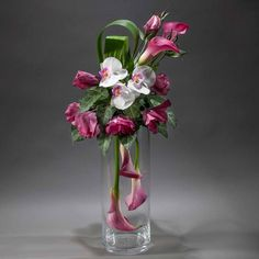 By florist Claudia Dora Oprina, of Dora Bloom. Eiffel Tower Vases, Hotel Decor, Arte Floral, Calla Lily, Wedding Centerpieces, Floral Arrangements, Orchids, Glass Vase, Bloom