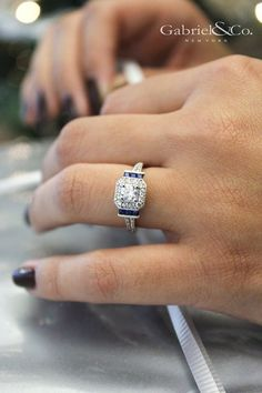 Gabriel & Co.-Voted Most Preferred Fine Jewelry and Bridal Brand. White G… Gabriel & Co.-Voted Most Preferred Fine Jewelry and Bridal Brand. White Gold Round 3 Stones halo Engagement Ring with sapphire sidestones Round Halo Engagement Rings, Designer Engagement Rings, Vintage Engagement Rings, Halo Rings, Diamond Rings, Engagement Rings With Sapphires, Solitaire Diamond, Sapphire Diamond, Blue Sapphire