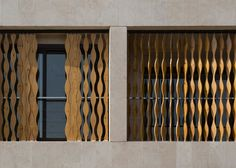 Wavy wooden shutters can be drawn across the pigeonhole-style windows of this apartment block in Tehran by local studio TDC Office