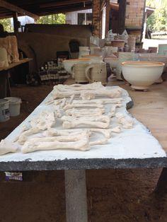 My porcelain Bones soaked in soda ash on kiln washed shelf awaiting anagama loading. Roger Jamison community