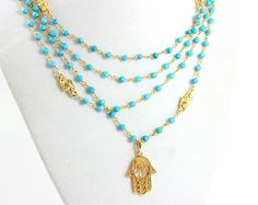 This hamsa necklace is even more stunning in person! Layers of beautiful Freshwater pearls around 3mm in size with turquoise beads. A very nice 18kt gold filled hamsa pendant hangs from these lovely layers. Necklace chain is 18kt gold filled. Hamsa pendant measures 25x17mm. Necklace layers measure 16-18 or 18-20 , 20-22 length with toggle closure. Comes nicely boxed, the perfect gift!  PLEASE READ....The pendant on this necklace has changed. You will receive the 18kt gold filled Hamsa…