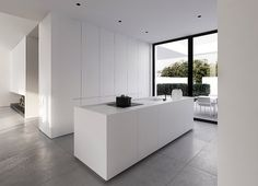 A sharp edged white island, accessorized with black, forms the centerpiece of the kitchen. All of the units are without handles to maintain ...