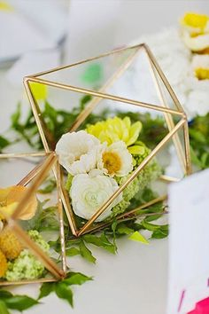 Fill up gilded prisms with florals or candles for captivating center pieces.