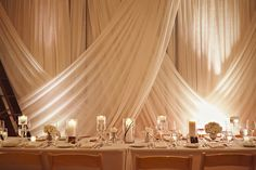 elegant gold winter wedding // wedding centerpieces with floating candles and varying white floral arrangements