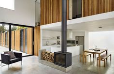 9 Wood Stove Fireplaces That Are Stoking Our Flames , modern minimal living room and dining room with wood stove fireplace. Home Fireplace, Fireplace Design, Contemporary Kitchen Design, Interior Design Kitchen, Double Sided Fireplace, Double Sided Stove, Long House, House 2, Freestanding Fireplace
