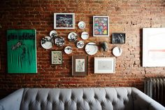 Create random groupings. The client had a vast collection of small pieces of art varying in style and subject. It lent itself perfectly to being clustered on the wall — which also helped provide alignment for the sofa. We used a set of skeleton plates to tie the framed selections together.