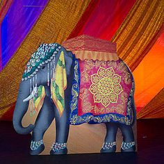 This Asian Elephant Standee features an elephant cutout with a beautiful jeweled headpiece and beaded ankle jewelry. Each Elephant cutout measures 7 1/4 ft high x 7 1/2 ft wide.