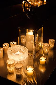 A chic lounge area is illuminated by a lantern, floating candles and numerous votive candles.