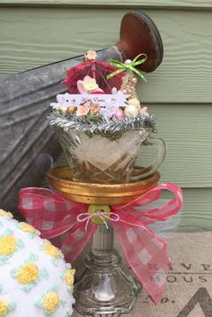 Here comes the Easter bunny! This centerpiece decoration features a pink flocked bunny with glittered bottle brush trees and a paper parasol nestled into a vintage pressed glass teacup. It sits atop a gold plant saucer and vintage crystal candlestick. A little treasure to be