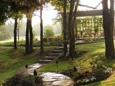 A stone pathway leads through a formal garden and up to a trellised gazebo that is surrounded in early morning mist
