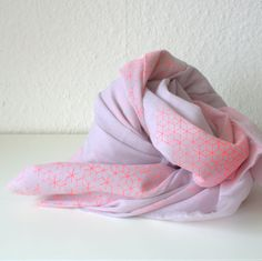 Graphic but feminine scarf with a neon coral star print on thin lavender cotton.Measures 175x75 cm.The materials are 100% cotton voile in a light lavender color that has been handprintet with silkscreens to add the graphic star print.  Every scarf is unique.Wash at 30 degrees and iron on max heat.Approx 53,57 Euro