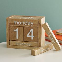 "Wooden Perpetual Calendar -- natural wood finish & clever, compact design, practical & fun to play with. Adjust the blocks to reveal the current date & day.  Solid wood;   Removable pieces adjust to correct date;   7""w x 6""d x 5""h,   Wipe clean.  Sold at West Elm $ 30 - no longer available"