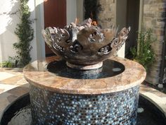 This stone and glass fountain with a Great Bowl O' Fire™ as centerpiece in San Clemente, CA shows that you can have it all… a stunning water feature crowned by live fire. Day or night, fire brings a lively focus to this water feature, combining two of the most primal elements. Colored lights on a timer illuminate the fountain and firebowl at night.