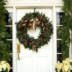 Ornamental Outdoors        ..this traditional wreath is complemented by the heavy garland and bright white flowers surrounding it. The dark, natural tones and elements of this wreath pop against the white door.