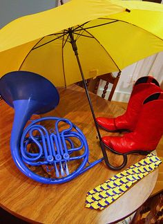 Yellow umbrella, blue french horn, red cowboy boots, and the ducky tie.