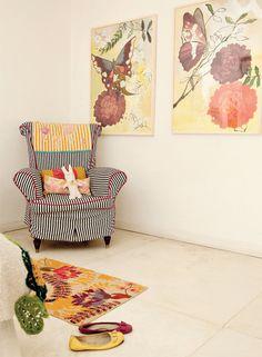 En una esquina del dormitorio, sorprende un sillón antiguo heredado que se vistió con una funda rayada. Los cuadros son de Loly Acuña.