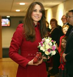 Catherine, who received a bouquet when she attended the Millenium stadium match, matched her claret-coloured coat with glossy hair