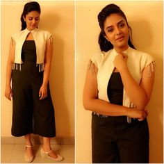 Sreemukhi in black culluottes jumpsuit and white opoen cape with fringe details.br>Thhe White cape with mega sleeves and fringes all over the ae is beautiful. 12 January 2018