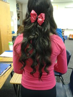 Curled hair pulled back with a cute bow.