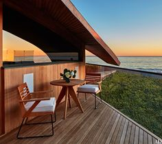 On the second level, the master suite terrace overlooks a green roof; the custom-made teak table and chairs are by Alwy Visschedyk for Summit, and the cushions are of a Holly Hunt fabric.