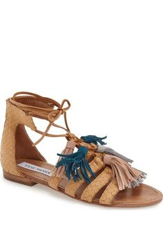 Flouncy tassels dance with every step on a snake-embossed leather sandal that offers a fresh, playful spin on a go-to gladiator silhouette.