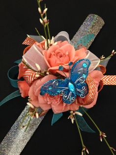 Seeing a lot of coral and teal dresses this year!  Coral spray roses with accents of fresh genestra and a lovely little butterfly.