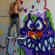 Chris Brown painting a mural.