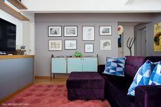 Sala de televisão com parede galeria pintada de cinza e decoração que apostou no uso de cores.