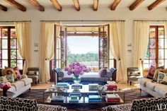 In an Ibiza home decorated by Audrey Carden, the beamed living room's beige linen sofas and the slipper chairs—the latter upholstered in a Raoul Textiles fabric—are all by George Smith.