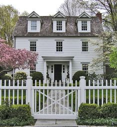 White picket fence and twisting topiaries.