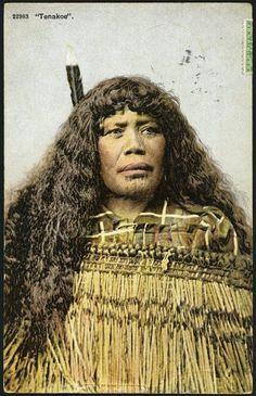 Postcard. Tenakoe 22983. [Maori woman. 1904-1914].  Shows a head  and shoulders portrait of a Maori women with long hair worn loose, chin  moko, flax cloak and huia feather in her hair.