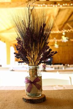 Rustic wedding- Table centerpieces: Mason Jars, wrapped with burlap, dried fall wheat, plum berries  stems, plum bow all on top of a wood slice!