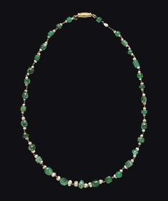 Lot Description A ROMAN GOLD, EMERALD AND PEARL NECKLACE  CIRCA 1ST CENTURY A.D.  Composed of lengths of chain with links threaded through emerald beads, some hexagonal, some spherical, a pearl on either side, some emeralds and pearls modern replacements; strung with a modern gold clasp 15¼ in. (38.7 cm.) long
