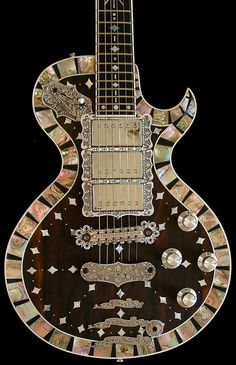 El Dorado:  Exquisite Ziricote (Mexican Rosewood) hand-inlaid top, surrounded by a mosaic of rare purple abalone and ebony, on a black Korina body; walnut neck with a theme-correct mother-of-pearl inlaid ebony board.