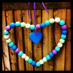 Heart made from wire coat hanger, strung with painted wooden beads and finished off with painted wooden heart & ribbon. Raw materials from Hobbycraft