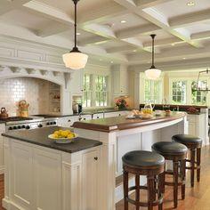 multi-level kitchen island + range hood + backsplash + pendant lights